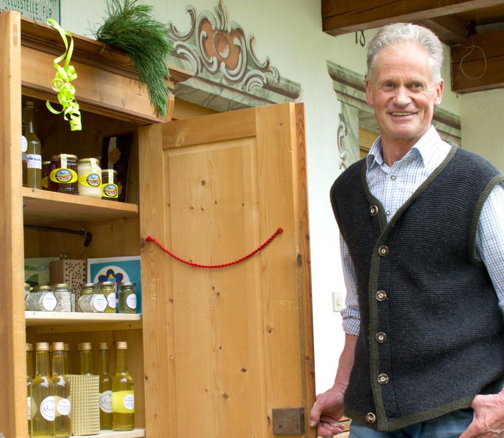 Ein alter Bauernschrank mit den Produkten steht vor der Tür beim Hof